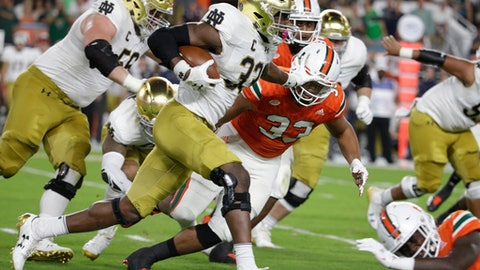 Notre Dame running back Josh Adams (33) runs as Miami defensive lineman Trent Harris (33) defends during the first half of an NCAA college football game, Saturday, Nov. 11, 2017, in Miami Gardens, Fla. (AP Photo/Lynne Sladky)
