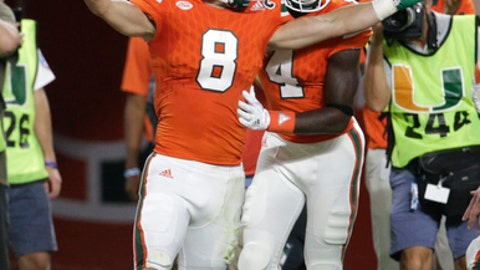 Miami wide receiver Braxton Berrios (8) celebrates with wide receiver Jeff Thomas (4) after scoring a touchdown during the first half of an NCAA college football game against Notre Dame, Saturday, Nov. 11, 2017, in Miami Gardens, Fla. (AP Photo/Lynne Sladky)