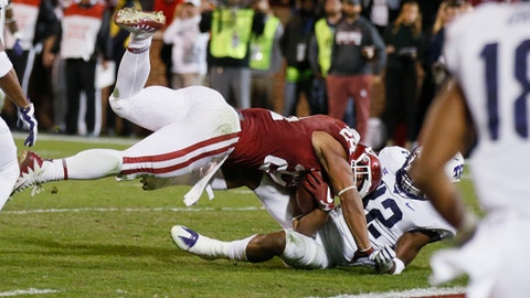Oklahoma running back Rodney Anderson, left, tumbles into the end zone with TCU linebacker Travin Howard, right, for a touchdown in the second quarter of an NCAA college football game in Norman, Okla., Saturday, Nov. 11, 2017. (AP Photo/Sue Ogrocki)
