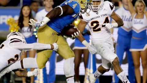 UCLA running back Bolu Olorunfunmi, right, breaks away form Arizona State defensive back Cody French during the first half of an NCAA college football game in Pasadena, Saturday, Nov. 11, 2017. (AP Photo/Chris Carlson)
