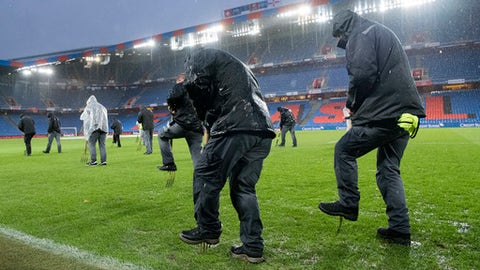 Staff members work under heavy rain to evacuate water from the pitch, prior the 2018 Fifa World Cup play-offs second leg soccer match between Switzerland and Northern Ireland at the St. Jakob-Park stadium in Basel, Switzerland, Sunday, Nov.12, 2017. (Jean-Christophe Bott/Keystone via AP)