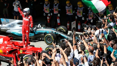 Ferrari driver Sebastian Vettel, of Germany, celebrates after winning the Brazilian Formula One Grand Prix at the Interlagos race track in Sao Paulo, Brazil, Sunday, Nov. 12, 2017. (AP Photo/Andre Penner)