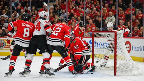 New Jersey Devils left wing Miles Wood (44) scores against Chicago Blackhawks goalie Corey Crawford (50) during the first period of an NHL hockey game Sunday, Nov. 12, 2017, in Chicago. (AP Photo/Kamil Krzaczynski)