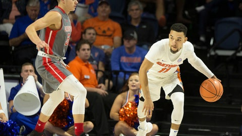 Florida guard Chris Chiozza (11) dribbles against the defense of Gardner-Webb guard Liam O'Reilly (5) during the first half of an NCAA college basketball game in Gainesville, Fla., Monday, Nov. 13, 2017. (AP Photo/Ron Irby)
