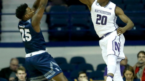 Northwestern 's Scottie Lindsey (20) blocks the shot of St. Peter's 's Cameron Jones during the first half of an NCAA college basketball game Monday, Nov. 13, 2017, in Rosemont, Ill. (AP Photo/Charles Rex Arbogast)
