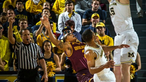 Michigan center Jon Teske, top, blocks a shot attempt from Central Michigan guard Shawn Roundtree, bottom left, in the second half of an NCAA college basketball game at Crisler Center in Ann Arbor, Mich., Monday, Nov. 13, 2017. Michigan won 72-65. (AP Photo/Tony Ding)