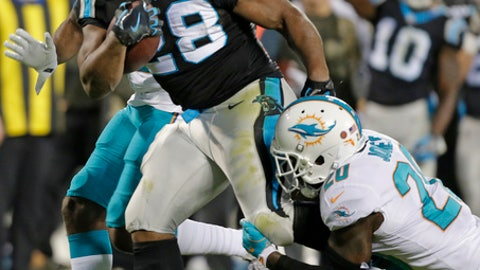 Carolina Panthers' Jonathan Stewart (28) runs as Miami Dolphins' Reshad Jones (20) defends in the first half of an NFL football game in Charlotte, N.C., Monday, Nov. 13, 2017. (AP Photo/Bob Leverone)
