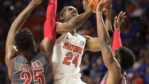 Florida guard Deaundrae Ballard (24) drives between Gardner-Webb forward DJ Laster (25) and guard Jaheam Cornwall during the second half of an NCAA college basketball game in Gainesville, Fla., Monday, Nov. 13, 2017. Florida won 116-74. (AP Photo/Ron Irby)