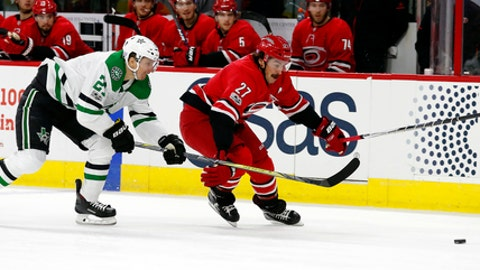 Carolina Hurricanes' Justin Faulk (27) races Dallas Stars' Antoine Roussel (21) for the loose puck during the first period of an NHL hockey game, Monday, Nov. 13, 2017, in Raleigh, N.C. (AP Photo/Karl B DeBlaker)