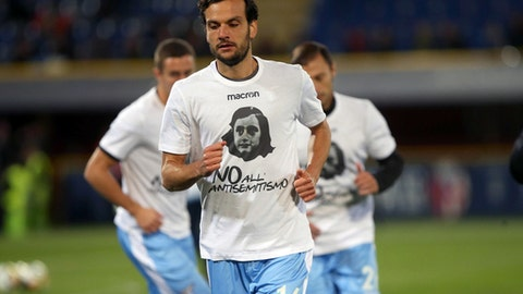 "FILE - In this Wednesday, Oct. 25, 2017 file photo, Lazio's Marco Parolo wears a t-shirt with an image of Anne Frank and reading in Italian ""No to Anti-semitism"" prior to the Serie A soccer match between Lazio and Bologna at the Renato Dall'Ara stadium in Bologna, Italy. The Italian football federation has called up Lazio to a hearing following the shocking scenes of anti-Semitism from the Serie A club's supporters last month. After their team's victory over Cagliari on Oct. 22, Lazio fans littered the Stadio Olimpico in Rome with images of Anne Frank, the young diarist who died in the Holocaust, wearing a jersey of city rival Roma. The FIGC says there was a ""clear anti-Semitic intent"" and that it ""constituted discriminatory behavior.""  (Giorgio Benvenuti/ANSA via AP)"