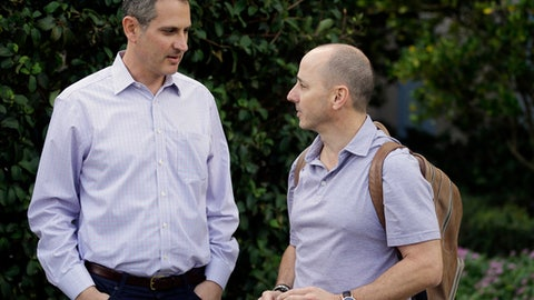 Thad Levine, left, general manager for the Minnesota Twins and New York Yankees general manager Brian Cashman, right, talk at the annual MLB baseball general managers' meetings, Tuesday, Nov. 14, 2017, in Orlando, Fla. (AP Photo/John Raoux)