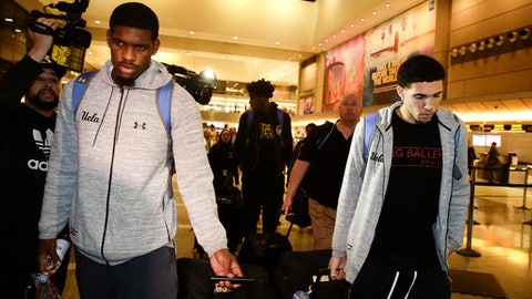 UCLA basketball players Cody Riley, left, LiAngelo Ball, right, and Jalen Hill, background center, are surrounded by the media as they leave the Los Angeles International Airport on Tuesday, Nov. 14, 2017, in Los Angeles. The three UCLA basketball players detained in China on suspicion of shoplifting returned home, where they may be disciplined by the school as a result of the international scandal. (AP Photo/Jae C. Hong)