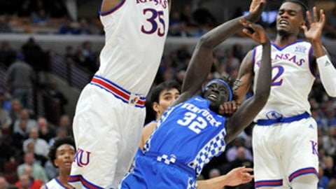 Kentucky forward Wenyen Gabriel (32) loses control of the ball as Kansas' Udoka Azubuike, left, and Lagerald Vick defend during the first half of an NCAA college basketball game Tuesday, Nov. 14, 2017, in Chicago. (AP Photo/Paul Beaty)