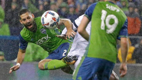 FILE - In this Nov. 3, 2017, file photo, Seattle Sounders' Clint Dempsey, left, kicks the ball away from Vancouver Whitecaps midfielder Aly Ghazal as Sounders' Harry Shipp (19) looks on during an MLS soccer Western Conference semifinal match in Seattle. Dempsey has been named the MLS Comeback Player of the Year after a heart condition in 2016 put his career in jeopardy. Dempsey was the choice after scoring 12 goals in the 2017 regular season and leading Seattle to a second-place finish in the MLS Western Conference. The Sounders will face Houston in the Western Conference finals beginning Nov. 21, 2017. (AP Photo/Ted S. Warren, file)