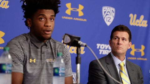 UCLA head coach Steve Alford, right, listens as Jalen Hill reads his statement during a news conference at UCLA Wednesday, Nov. 15, 2017, in Los Angeles. Three UCLA NCAA college basketball players accused of shoplifting in China admitted to the crime and apologized before coach Steve Alford announced they were being suspended indefinitely. (AP Photo/Jae C. Hong)