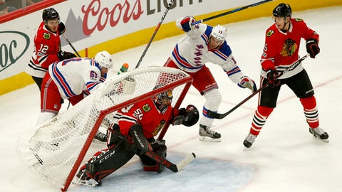 The net almost falls over onto Chicago Blackhawks goalie Corey Crawford as Alex DeBrincat (12) and New York Rangers' Rick Nash battle behind, while Kevin Hayes (13) and Connor Murphy (5) watch during the second period of an NHL hockey game, Wednesday, Nov. 15, 2017, in Chicago. (AP Photo/Charles Rex Arbogast)