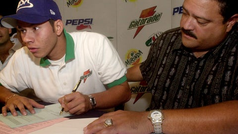 """FILE - In this Oct. 21, 2004, file photo, Nicaragua's Carlos Teller, left, signs a contract with the Pittsburgh Pirates as scout Rene Gayo sits next to him in San Salvador, El Salvador. The Pirates say Major League Baseball intends to discipline Gayo, their director of Latin American scouting, for rules violations, and the team announced it will not renew his contract when it expires next month. The Pirates said in a statement Wednesday, Nov. 15, 2017, that they have a """"profound disappointment in the breach of trust that was the subject of MLB's investigation."""" (AP Photo/Luis Romero, File)"""