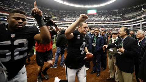 FILE - In this Nov. 21, 2016, file photo, Oakland Raiders quarterback Derek Carr, center, and defensive end Khalil Mack (52) leave the field after an NFL football game against the Houston Texans in Mexico City. The Raiders return to Mexico City to face the New England Patriots this week. (AP Photo/Eduardo Verdugo, File)