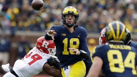 FILE - In this Oct. 28, 2017, file photo, Michigan quarterback Brandon Peters (18) throws while pressured by Rutgers linebacker Brandon Russell (49) during the second half of an NCAA college football game in Ann Arbor, Mich. Peters' play has helped Michigan win three straight games, scoring 35 in each. No. 5 Wisconsin will face its sternest test yet this season when No. 19 Michigan visits Camp Randall Stadium in the home season finale. (AP Photo/Carlos Osorio)