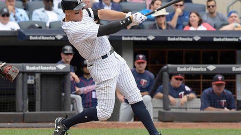 FILE - In this Sept. 10, 2017, file photo, New York Yankees' Aaron Judge hits a two-run home run during the third inning of a baseball game against the Minnesota Twins in New York. Houston dynamo Jose Altuve and Yankees slugger Aaron Judge are the favorites for the AL MVP award while Miami Marlins' Giancarlo Stanton is the top candidate for the NL prize.  (AP Photo/Bill Kostroun)