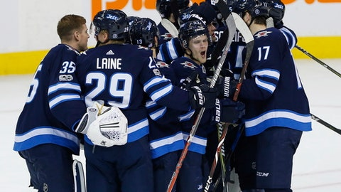 Winnipeg Jets' Nikolaj Ehlers, centre, and teammates celebrate after defeating the Philadelphia Flyers in a shootout in NHL hockey game action in Winnipeg, Manitoba, Thursday, Nov. 16, 2017. (John Woods/The Canadian Press via AP)