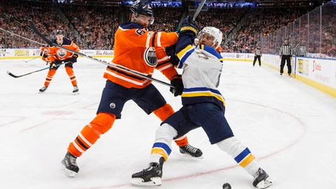 St. Louis Blues' Jaden Schwartz (17) and Edmonton Oilers' Adam Larsson (6) vie for the puck during the third period of an NHL hockey game Thursday, Nov. 16, 2017, in Edmonton, Alberta. (Jason Franson/The Canadian Press via AP)