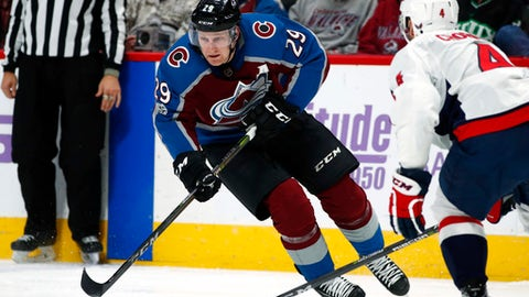 Colorado Avalanche center Nathan MacKinnon, left, drives down the ice with the puck as Washington Capitals defenseman Taylor Chorney drops back to defend during the third period of an NHL hockey game Thursday, Nov. 16, 2017, in Denver. Colorado won 6-2. (AP Photo/David Zalubowski)