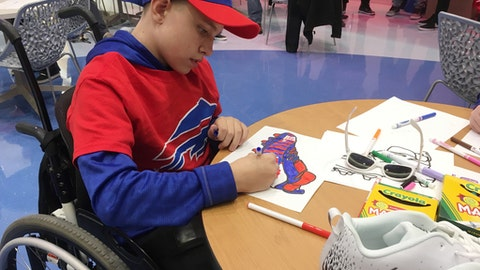 """Ian Cameron, a pediatric cancer patient at Buffalo's John R. Oishei Children's Hospital, joined Buffalo Bills players on Tuesday, Nov. 14, 2017, to customize cleats, which players will wear during their home game against the New England Patriots on Dec. 3. The event was held as part of the NFL's """"My Cause, My Cleats"""" campaign in which players are allowed to wear their own style of footwear reflecting their commitment to charitable causes. (Photo by John Wawrow)"""