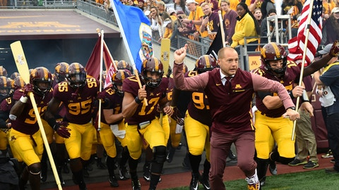 FILE - In this Oct. 21, 2017, file photo, Minnesota coach P.J. Fleck leads his team onto the field for an NCAA college football game against Illinois in Minneapolis. Minnesota faces Northwestern this week. Fleck recalls the advice about running a program he got from Northwestern's Pat Fitzgerald over lunch many years ago. It still resonates. (AP Photo/John Autey, File)