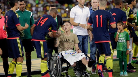 FILE - In this file photo dated Wednesday, Jan. 25, 2017, former Chapecoense goalkeeper Follmann, in wheelchair, greets various Colombia's soccer players prior to a friendly match at the Nilton Santos stadium in Rio de Janeiro, Brazil, in tribute to Chapecoense soccer players who died in a plane crash in Colombia last November. Follmann survived the crash.  Chapecoense player Tulio de Melo said Friday Nov. 17, 2017, that the team have honored the memory of their dead teammates, by avoiding relegation in the Brazilian championship, one year after an air crash killed 19 of its players. (AP Photo/Silvia Izquierdo, FILE)