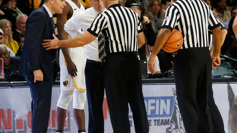 Virginia coach Tony Bennett, left, and Virginia Commonwealth coach Mike Rhoades listen to an official late in the second half of an NCAA college basketball game in Richmond, Va., Friday Nov. 17, 2017. (Mark Gormus/Richmond Times-Dispatch via AP)