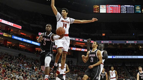 Omaha guard KJ Robinson (5) attempts a layup past the defense of Louisville forward Anas Mahmoud (14) during the first half of an NCAA college basketball game, Friday, Nov. 17, 2017, in Louisville, Ky. (AP Photo/Timothy D. Easley)