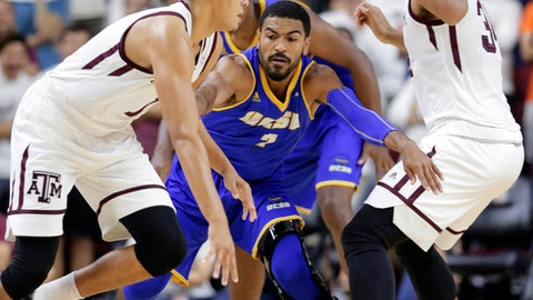 Texas A&M forward DJ Hogg (1) drives around UC Santa Barbara guard Gabe Vincent (2) as he is blocked by Texas A&M center Tyler Davis (34) during the first half of an NCAA college basketball game Friday, Nov. 17, 2017, in College Station, Texas. (AP Photo/Michael Wyke)
