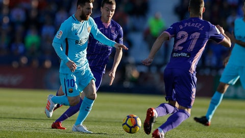 Barcelona's Lionel Messi, left, battles for the ball with Leganes' Ruben Perez during the Spanish La Liga soccer match between Barcelona and Leganes at the Butarque stadium in Madrid, Saturday, Nov 18, 2017. (AP Photo/Francisco Seco)