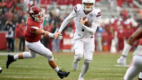 Mississippi State quarterback Nick Fitzgerald slips past Arkansas defender Grant Morgan to score a touchdown during the first half of an NCAA college football game Saturday, Nov. 18, 2017, in Fayetteville, Ark. (AP Photo/Michael Woods)