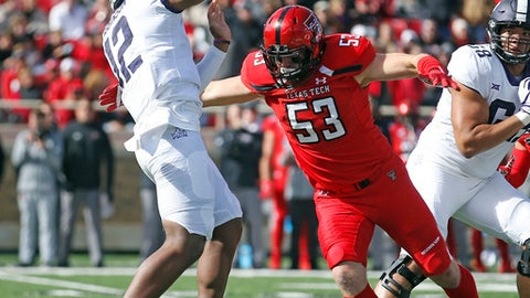 Texas Tech's Eli Howard (53) moves in as TCU's Shawn Robinson (12) throws a pass during the first half of the NCAA college football game Saturday, Nov. 18, 2017, in Lubbock, Texas. (AP Photo/Brad Tollefson)