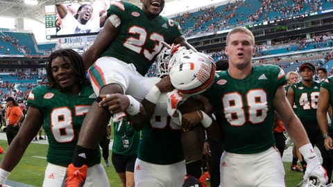 Miami tight end Christopher Herndon IV (23) is carried off the field by his teammates after an NCAA college football game against Virginia, Saturday, Nov. 18, 2017, in Miami Gardens, Fla. Miami won 44-28. (AP Photo/Lynne Sladky)