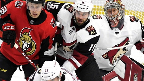 Arizona Coyotes goaltender Antti Raanta (32) tries to look past teammates Alex Goligoski (33) and Brad Richardson (15) and Ottawa Senators' Ryan Dzingel (18) during the second period of an NHL hockey game in Ottawa, Saturday, Nov. 18, 2017. (Justin Tang/The Canadian Press via AP)