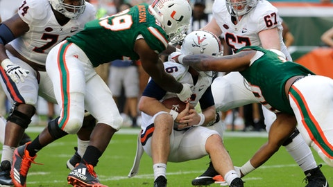 Miami defensive lineman Joe Jackson, left, and defensive lineman RJ McIntosh, right, sack Virginia quarterback Kurt Benkert (6) during the second half of an NCAA college football game, Saturday, Nov. 18, 2017, in Miami Gardens, Fla. Miami won 44-28. (AP Photo/Lynne Sladky)