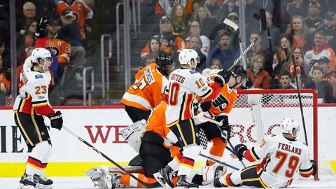 Calgary Flames' Sean Monahan, left, reacts to his second goal during the second period of an NHL hockey game against the Philadelphia Flyers, Saturday, Nov. 18, 2017, in Philadelphia. The Flames won 5-4 in overtime. (AP Photo/Chris Szagola)