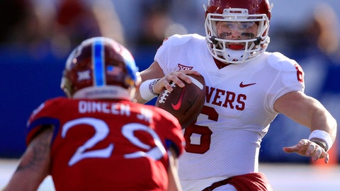 Oklahoma quarterback Baker Mayfield (6) tries to avoid Kansas linebacker Joe Dineen Jr. (29) during the first half of an NCAA college football game in Lawrence, Kan., Saturday, Nov. 18, 2017. (AP Photo/Orlin Wagner)