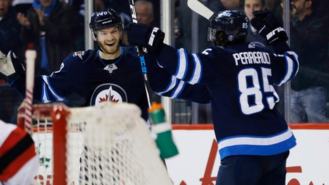 Winnipeg Jets' Joel Armia (40) and Mathieu Perreault (85) celebrate Perreault's goal against the New Jersey Devils during the second period of an NHL hockey game in Winnipeg, Manitoba, Saturday, Nov. 18, 2017. (John Woods/The Canadian Press via AP)