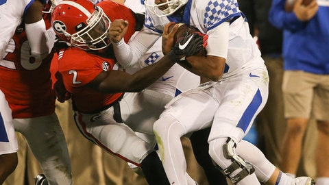Kentucky quarterback Stephen Johnson (15) is stopped by Georgia defensive back Richard LeCounte III (2) after a short gain in the second half of an NCAA college football game Saturday, Nov. 18, 2017, in Athens, Ga. Georgia won 42-13. (AP Photo/John Bazemore)