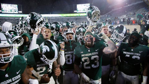 Michigan State players, including from left, Darrell Stewart, Gerald Holmes (24), Damion Terry (behind Holmes), Trishton Jackson, Chris Frey (23), Matt Sokol, right rear, and Shane Jones, celebrate following a 17-7 win over Maryland in an NCAA college football game, Saturday, Nov. 18, 2017, in East Lansing, Mich. (AP Photo/Al Goldis)