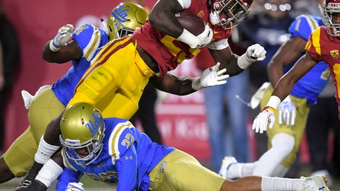 Southern California running back Ronald Jones II, top, is tackled by UCLA defensive back Nate Meadors during the first half of an NCAA college football game, Saturday, Nov. 18, 2017, in Los Angeles. (AP Photo/Mark J. Terrill)