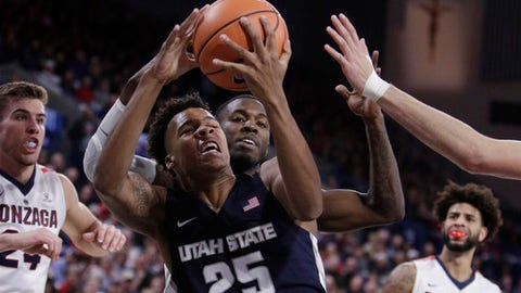 Utah State forward Dwayne Brown Jr. (25) grabs a rebound in front of teammate guard DeAngelo Isby during the first half of an NCAA college basketball game against Gonzaga in Spokane, Wash., Saturday, Nov. 18, 2017. (AP Photo/Young Kwak)