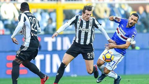 Juventus forward Federico Bernardeschi, center, and Sampdoria forward Fabio Quagliarella vie for the ball during the Italian Serie A soccer match between Sampdoria and Juventus at the Luigi Ferraris Stadium in Genoa, Italy, Sunday, Nov. 19 2017. (Simone Arveda/ANSA via AP)