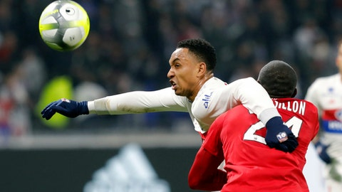 Lyon's Kenny Tete, left, challenges for the ball with Montpellier's Jerome Roussillon, right, during their French League One soccer match in Decines, near Lyon, central France, Sunday, Nov. 19, 2017. (AP Photo/Laurent Cipriani)