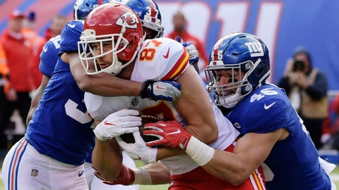 Kansas City Chiefs tight end Travis Kelce (87) is tackled by New York Giants' Ross Cockrell (37) and Calvin Munson (46) during the first half of an NFL football game Sunday, Nov. 19, 2017, in East Rutherford, N.J. (AP Photo/Bill Kostroun)