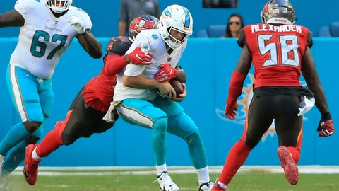 Miami Dolphins quarterback Jay Cutler (6) is taken down by Tampa Bay Buccaneers defensive end Ryan Russell (95) late in the second quarter of an NFL football game Sunday, Nov. 19, 2017 in Miami. Cutler left the game with a head injury. (Al Diaz/Miami Herald via AP)